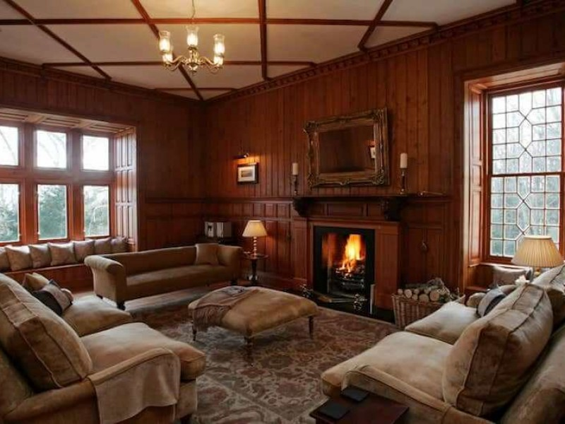 Wood lined drawing room with comfy sofas and log fire