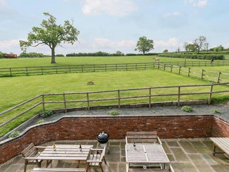 The Piano Barn Patio and Garden Area At Newborough Cottages