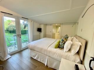 Ensuite bedroom in Annexe, doors to veranda overlooking gardens