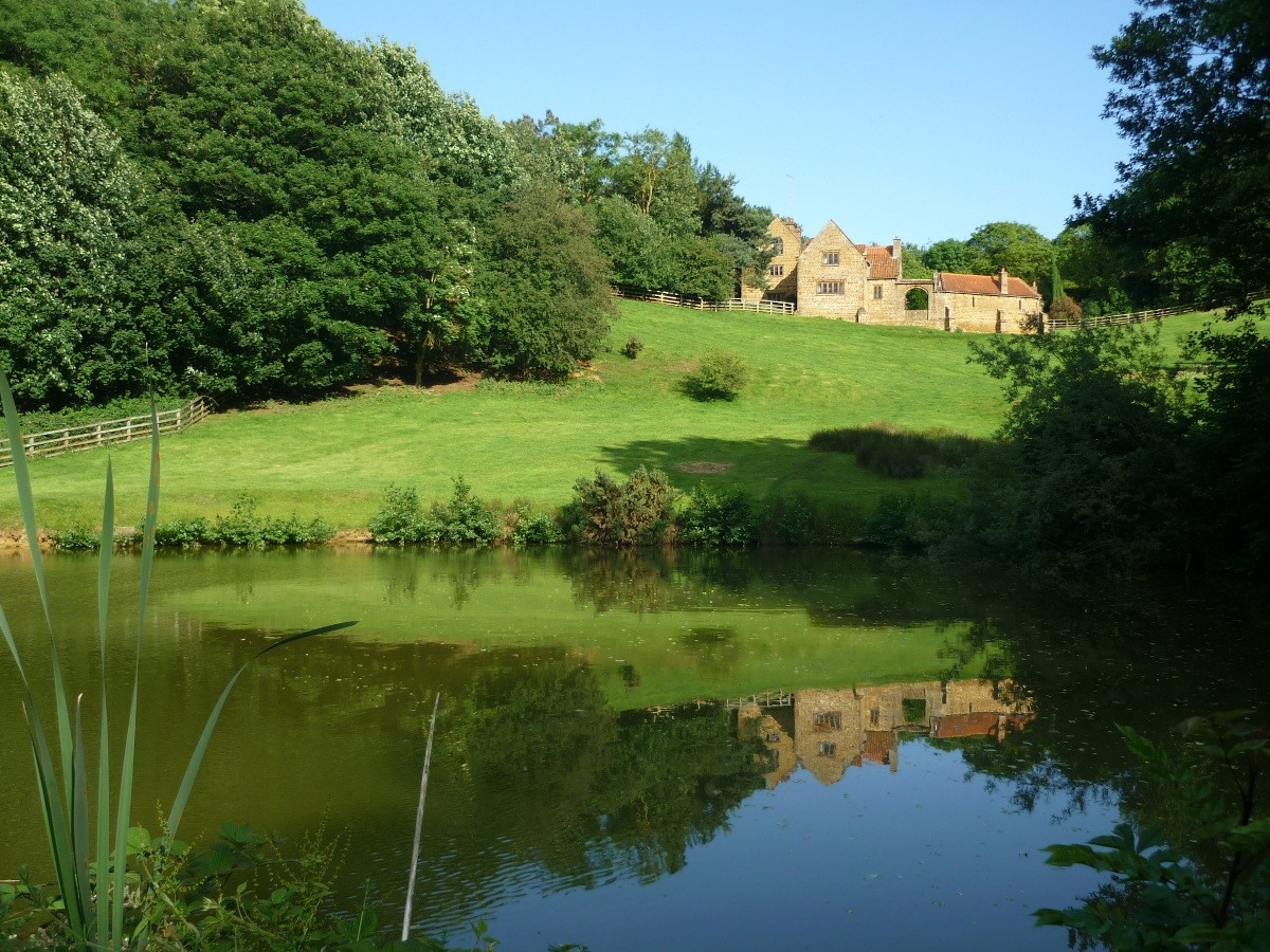 Heath Farm Holiday cottages reflected in the lake